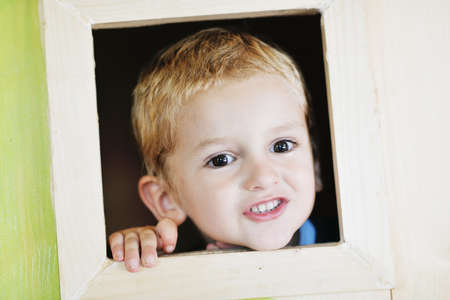 happy cute child in a wooden window at playground Stock Photo - 13710221