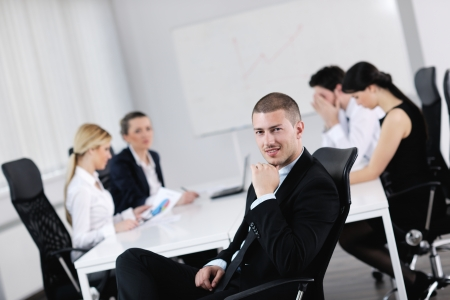 Portrait of a handsome young business man with people  in background at office meeting Stock Photo - 13774373