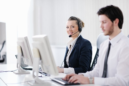 telephone headsets: business people group with  headphones giving support in  help desk office to customers, manager giving training and education instructions Stock Photo