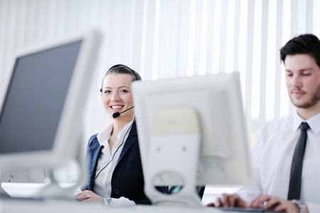 hotline: business people group with  headphones giving support in  help desk office to customers, manager giving training and education instructions Stock Photo