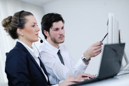 sales call: business people group with  headphones giving support in  help desk office to customers, manager giving training and education instructions Stock Photo