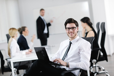 man sit: Portrait of a handsome young business man with people  in background at office meeting Stock Photo