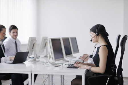 telemarketer: business people group with  headphones giving support in  help desk office to customers, manager giving training and education instructions Stock Photo