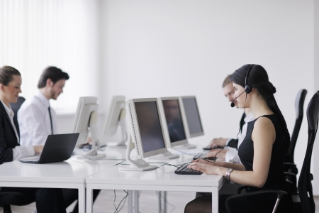 computer support: business people group with  headphones giving support in  help desk office to customers, manager giving training and education instructions Stock Photo