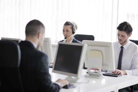 helpline: business people group with  headphones giving support in  help desk office to customers, manager giving training and education instructions Stock Photo