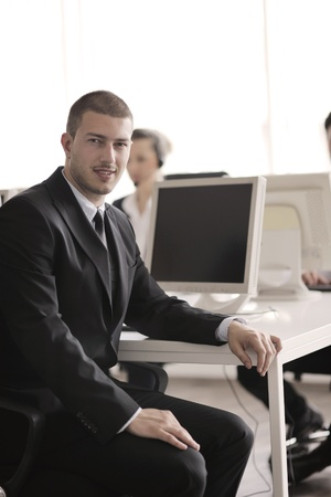 computer center: business people group with  headphones giving support in  help desk office to customers, manager giving training and education instructions Stock Photo