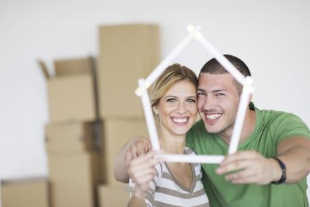 Jeune couple heureux se déplaçant dans la nouvelle maison Banque d'images