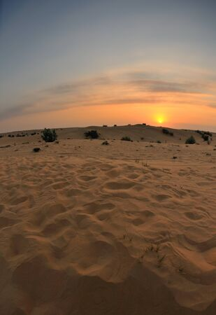 sunset with blue sky and clouds over sand dunes in sahara desert photo