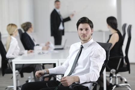hombres trabajando: Retrato de un hombre de negocios joven hermoso con la gente en fondo en la reuni�n de la oficina
