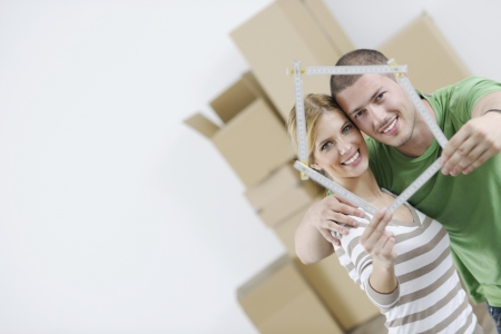 cardboard house: happy Young couple moving in new home Stock Photo