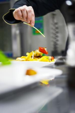 gourmet dinner: hermosa joven chef prepare la mujer y la comida sabrosa decoraci�n en la cocina