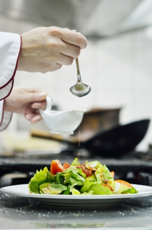 commercial kitchen: beautiful young chef woman prepare and decorating tasty food in kitchen