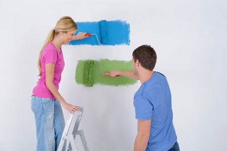 happy young couple paint in green and blue color white wall of their new home Stock Photo - 14108076