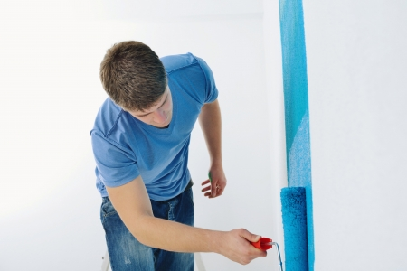 handsome young man paint in blue and green color  white wall of new home Stock Photo - 14107912