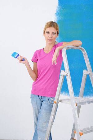 happy smiling woman painting interior white  wall in blue and green color of new house Stock Photo - 14108079
