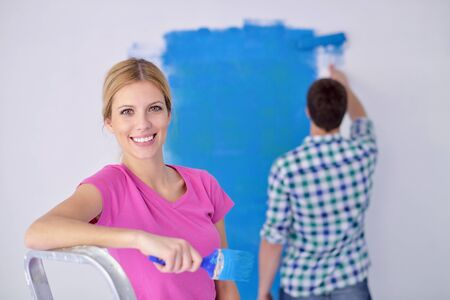 happy young couple paint in green and blue color white wall of their new home Stock Photo - 14108123