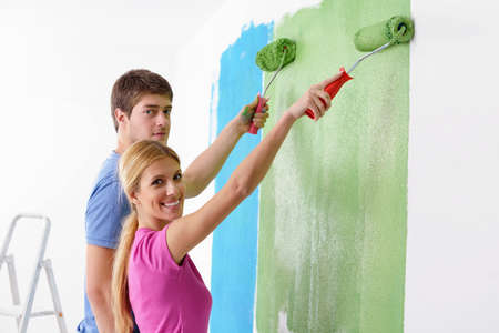 happy couple paint wall at new home photo