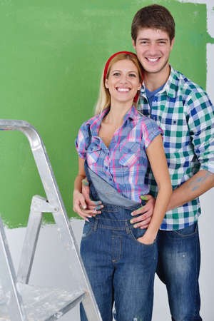 happy young couple paint in green and blue color white wall of their new home Stock Photo - 14108244