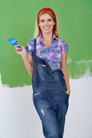 happy smiling woman painting interior white  wall in blue and green color of new house photo