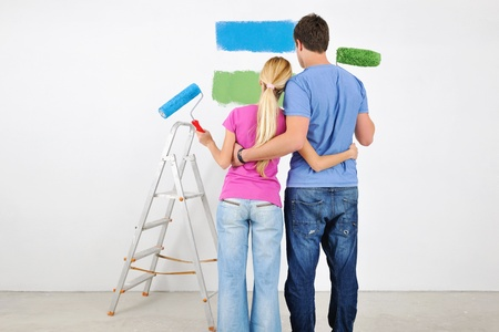 happy young couple paint in green and blue color white wall of their new home photo