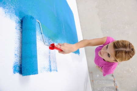 happy smiling woman painting interior white  wall in blue and green color of new house Stock Photo - 14169646