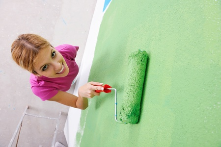 happy smiling woman painting interior white  wall in blue and green color of new house Stock Photo - 14170075