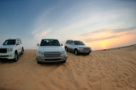 Desert Safari - Off-road jeep vehicles driving in the Arabian Desert at sunset photo