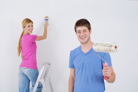 happy young couple paint in green and blue color white wall of their new home Stock Photo - 14170350
