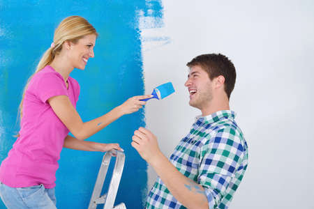 happy young couple paint in green and blue color white wall of their new home Stock Photo - 14171336