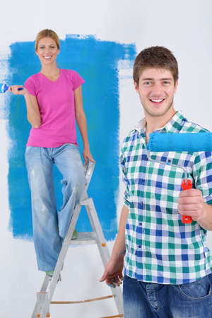 happy young couple paint in green and blue color white wall of their new home Stock Photo - 14171425