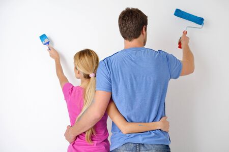 happy young couple paint in green and blue color white wall of their new home Stock Photo - 14170709