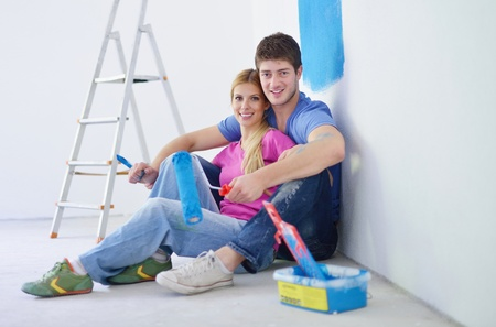 happy young couple relax after painting white wall in green and blue color in their new home photo