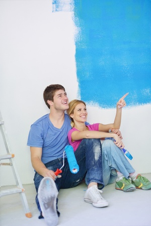 house wife: happy young couple relax after painting white wall in green and blue color in their new home