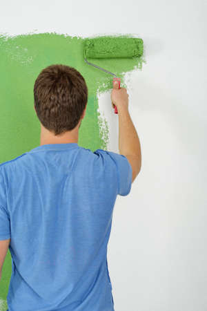 white color worker: handsome young man paint in blue and green color  white wall of new home