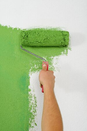 handsome young man paint in blue and green color  white wall of new home Stock Photo - 14172839