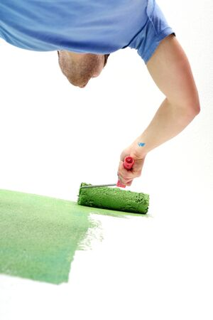 handsome young man paint in blue and green color  white wall of new home photo