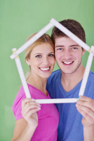 happy young couple paint in green and blue color white wall of their new home Stock Photo - 14170870