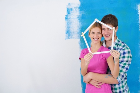 happy young couple paint in green and blue color white wall of their new home Stock Photo - 14170721