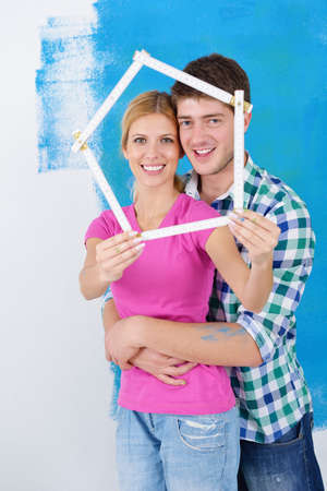 happy young couple paint in green and blue color white wall of their new home Stock Photo - 14172299