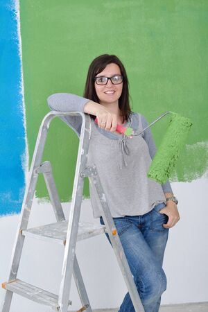 roller brush: happy smiling woman painting interior white  wall in blue and green color of new house Stock Photo