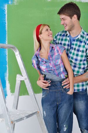 happy young couple paint in green and blue color white wall of their new home Stock Photo - 14173423