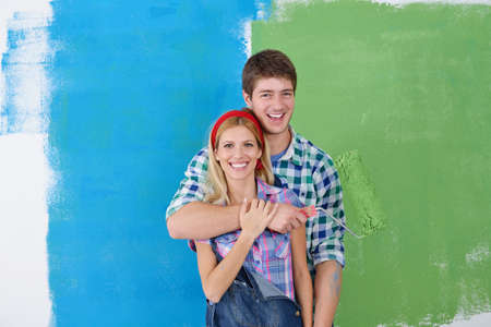 happy young couple paint in green and blue color white wall of their new home Stock Photo - 14171416