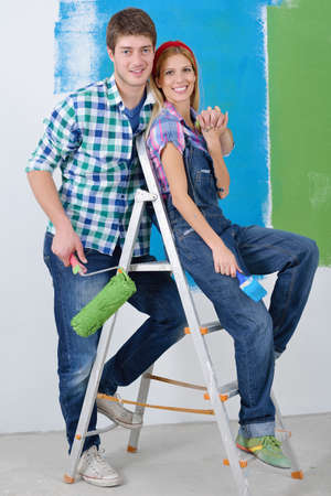 happy young couple paint in green and blue color white wall of their new home Stock Photo - 14173076