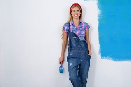 happy smiling woman painting interior white  wall in blue and green color of new house Stock Photo - 14173465