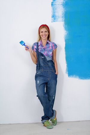 painter girl: happy smiling woman painting interior white  wall in blue and green color of new house Stock Photo