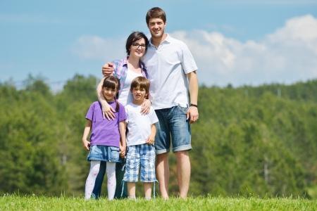 familias unidas: familia de joven feliz con sus hijos divertirse y relajarse al aire libre en la naturaleza con el cielo azul en el fondo