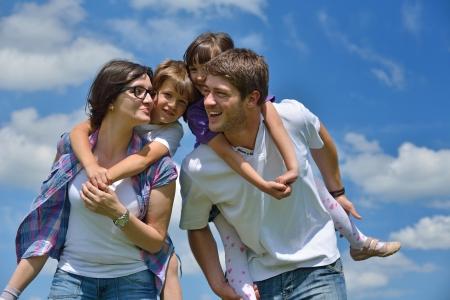happy families: joven familia feliz con sus hijos divertirse y relajarse al aire libre en la naturaleza con el cielo azul en el fondo Foto de archivo