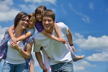 happy young family with their kids have fun and relax outdoors in nature with blue sky in background photo