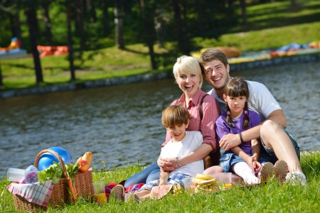picnic park: Happy young  family playing together with kids and eat healthy food  in a picnic outdoors