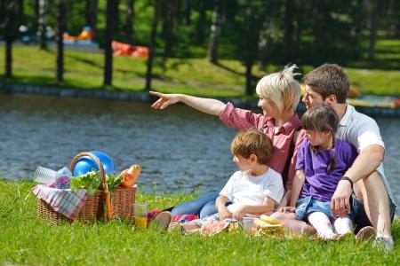 family picnic: Familia de joven feliz jugando juntos con los niños a comer alimentos saludables en un picnic al aire libre